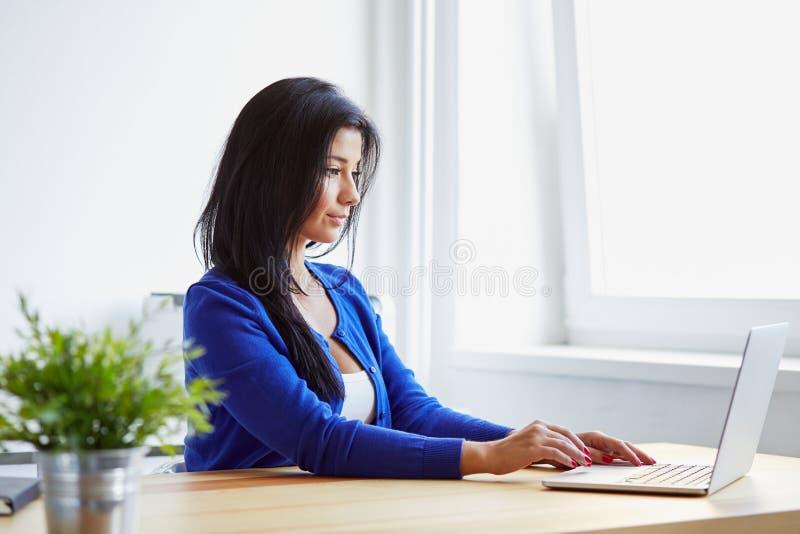 键入在膝上型计算机的妇女在办公室 免版税库存照片