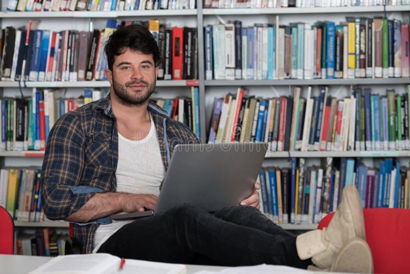 键入在膝上型计算机的男学生在大学图书馆里 库存照片