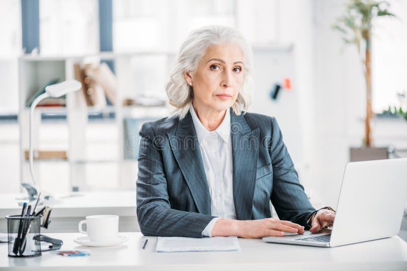 键入在膝上型计算机的确信的女实业家在工作场所在现代办公室 库存图片