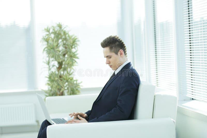 键入在膝上型计算机的英俊的商人坐在办公室的大厅 免版税库存照片