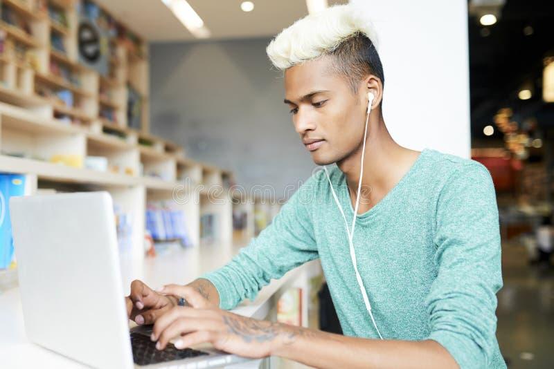 键入在膝上型计算机的英俊的学生 免版税库存照片