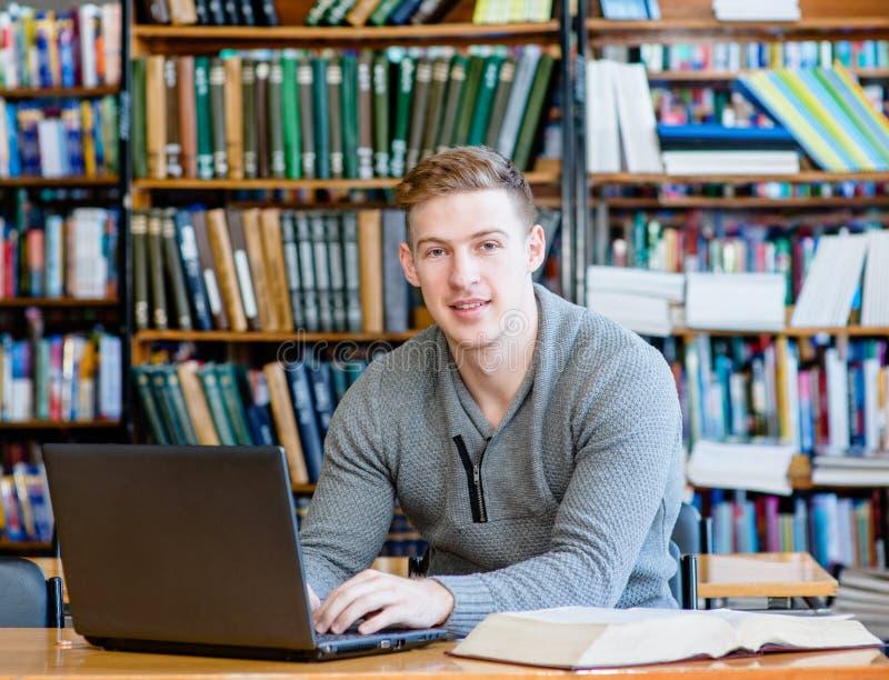 键入在膝上型计算机的年轻男学生在大学图书馆里 库存照片