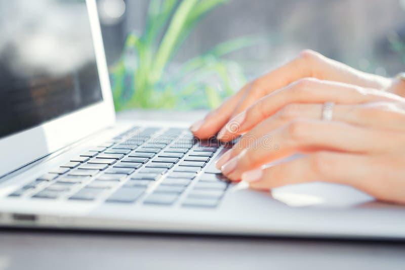 键入在膝上型计算机键盘关闭的女性手  在计算机的妇女工作 图库摄影