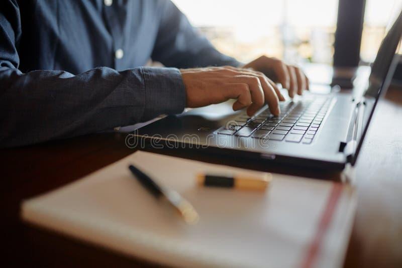 键入在膝上型计算机键盘和使用触感衰减器的白种人男性手特写镜头照片  笔记本和笔在前景  图库摄影