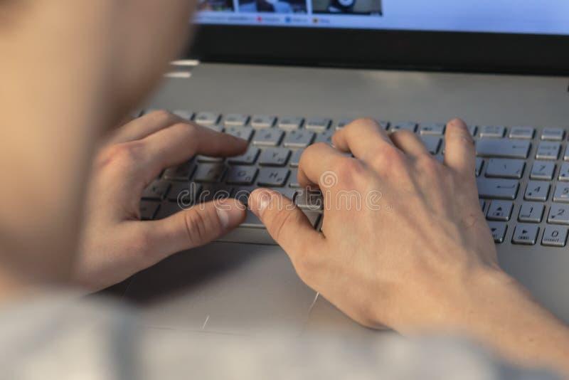 键入在膝上型计算机键盘的年轻人 背面图,软的焦点 辛苦在家 免版税库存照片