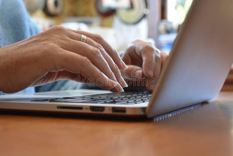 键入在膝上型计算机键盘,关闭的妇女  库存图片