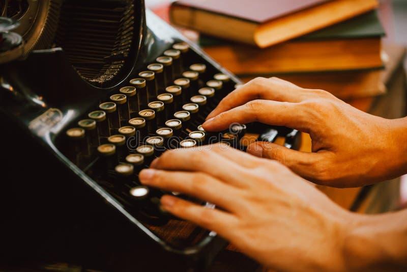 键入在葡萄酒的人的手键入作家机器和堆在木桌-非常选择聚焦上的书 免版税库存图片
