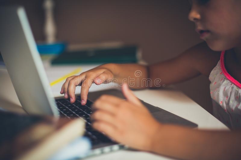 键入在计算机上的小女孩 库存照片