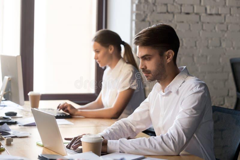 键入在计算机工作的千福年的办公室工作者在共有的办公室 库存照片