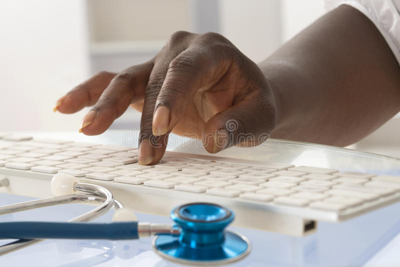 键入在键盘的非洲女性医生手 免版税库存照片