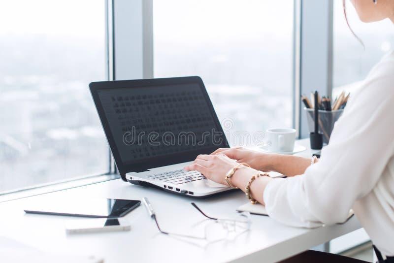 键入特写镜头观点的一个女性的办公室工作者,与新的项目一起使用在她的工作场所,使用膝上型计算机和Wi-Fi 免版税图库摄影