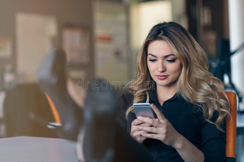 键入的企业消息 拿着巧妙的电话和看它与微笑的聪明的便衣的确信的少妇 库存照片