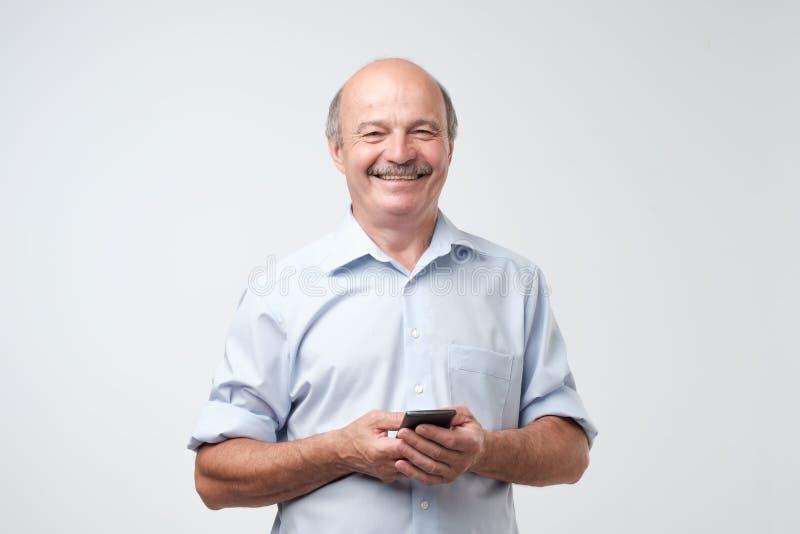 键入的正文消息 有站立在白色的髭的微笑的老人隔绝了背景 免版税库存照片