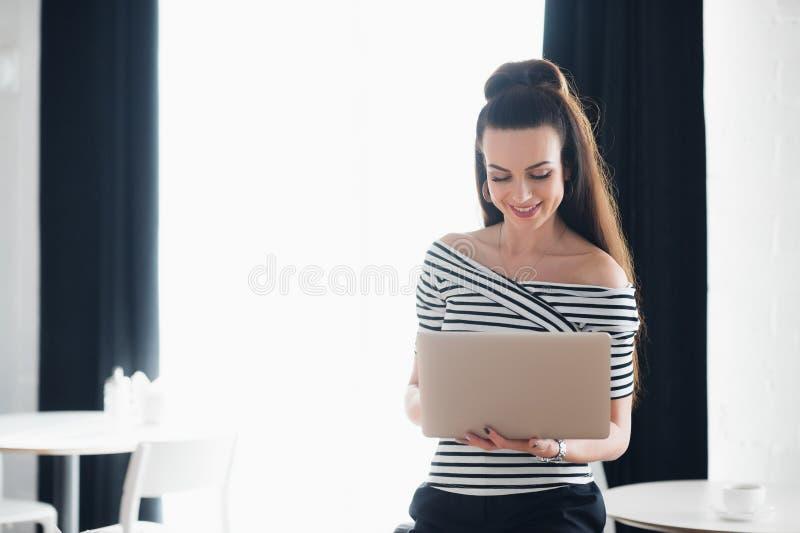 键入年轻可爱的深色的妇女拿着膝上型计算机和,当看屏幕时 成年女性冲浪 免版税库存照片