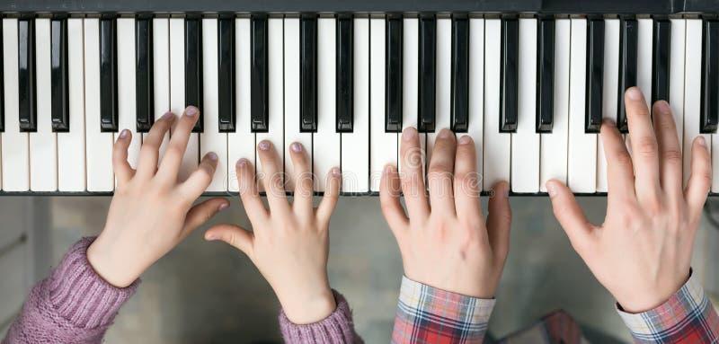 琴键孩子和母亲的顶视图和手 库存照片