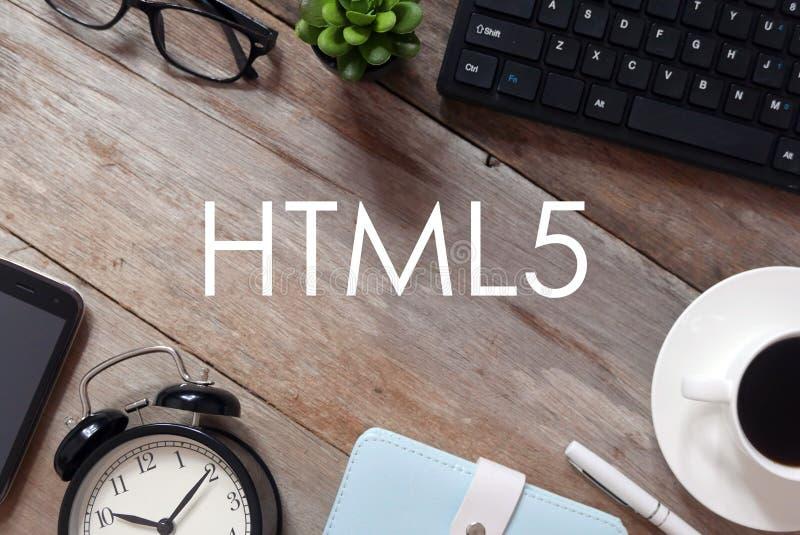 键盘、植物、太阳镜、一杯咖啡,笔、笔记本、时钟和手机顶视图在木背景写与HTML5 库存照片
