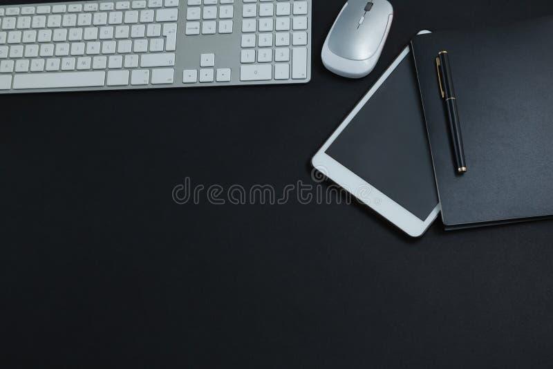 键盘、老鼠、数字式片剂、笔和组织者黑背景的 图库摄影