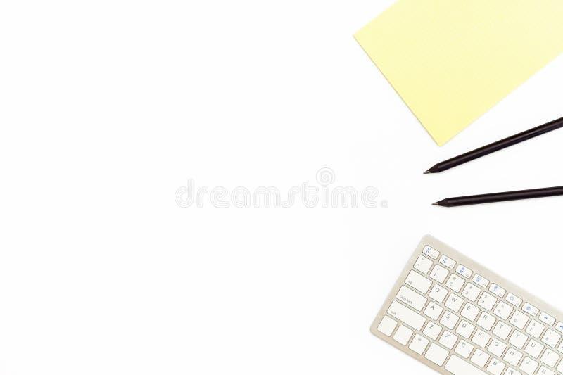 键盘、黄色笔记本和两黑铅笔在白色背景 企业工作场所的最小的概念 平的位置 库存照片