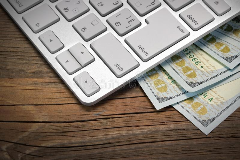 键盘和美元现金在木背景 免版税库存图片