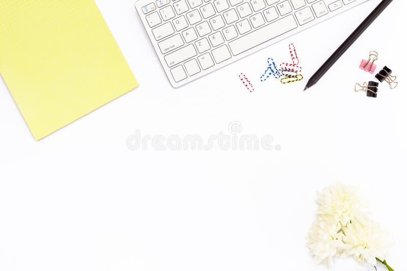 键盘,黄色笔记薄,菊花花,纸,纸夹和黑铅笔的夹子在白色背景 最小浓缩 图库摄影