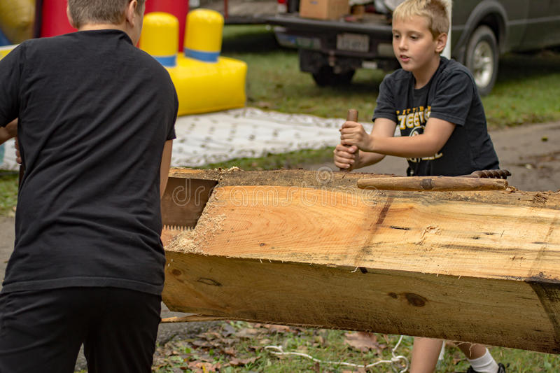 锯一本方形的日志的两个男孩在遗产节日 免版税图库摄影