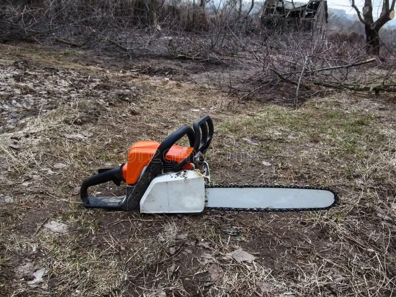锯在空的地面特写镜头说谎,并且有裁减分支在背景的庭院里 关心的概念和 免版税图库摄影