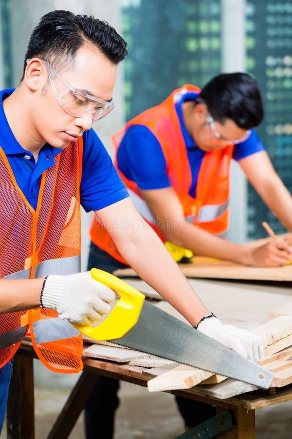 锯大厦或建造场所的木板建造者 免版税图库摄影