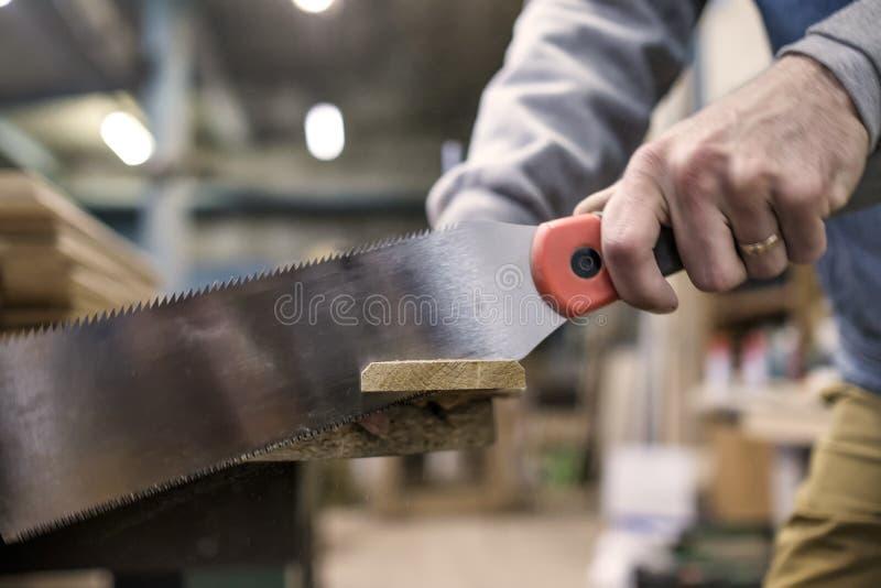 锯有特别日本手锯或引形钢锯的一个木板在木匠业期间 免版税库存图片