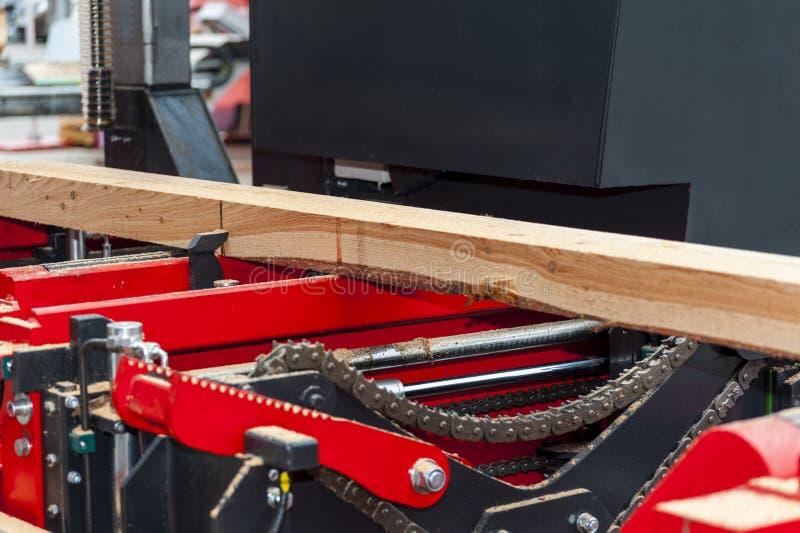 锯木厂 加工的过程注册设备锯木厂机器看见了锯在板条板的树干 图库摄影