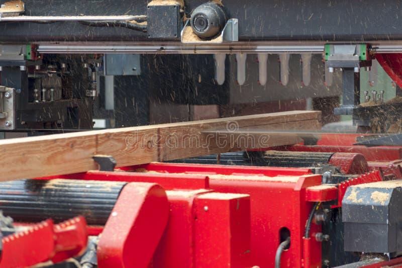 锯木厂 加工的过程注册设备锯木厂机器看见了锯在板条板的树干 免版税库存照片