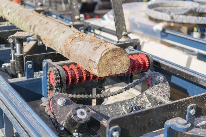 锯木厂 加工的过程注册设备锯木厂机器看见在板条的树干上的锯 木锯木屑工作锯 免版税图库摄影