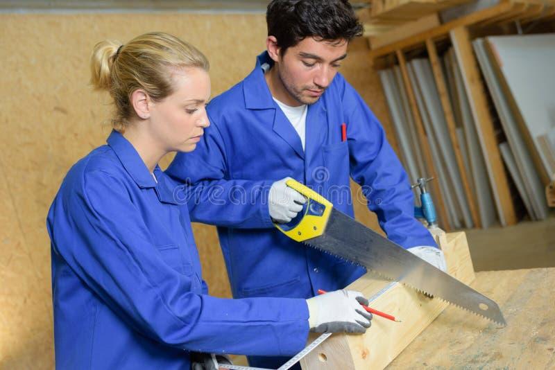 锯通过木头的年轻木匠 库存照片