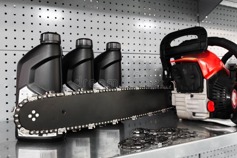 锯,在工具商店的油瓶显示 免版税库存照片