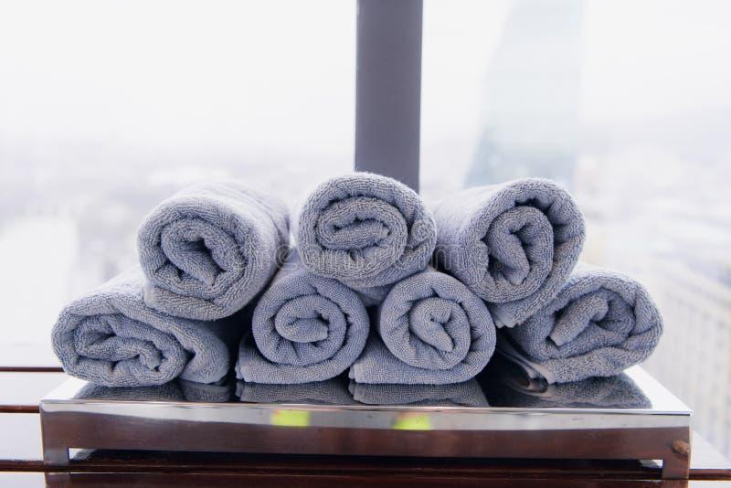 锻炼、体育和锻炼的滚动的白色健身健身房毛巾在一个长木凳 免版税库存照片