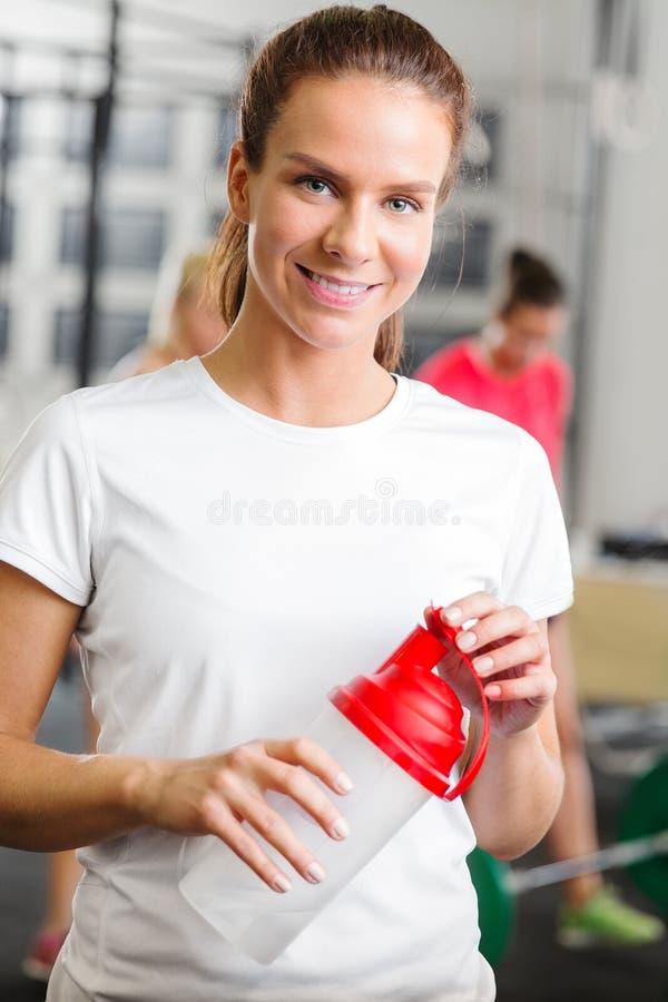 锻炼的微笑的妇女装备拿着一个饮用的瓶在健身健身房 库存图片