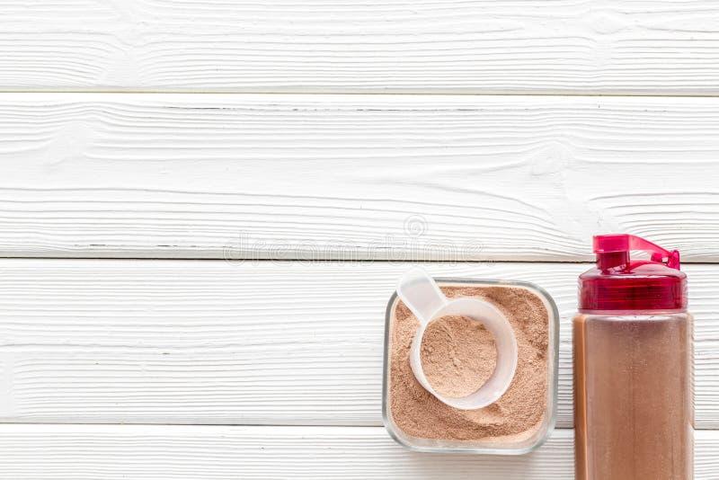 锻炼的营养与蛋白质鸡尾酒粉末和振动器在白色木背景顶视图大模型 免版税库存图片
