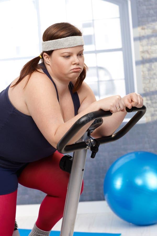锻炼脚踏车的用尽的肥胖妇女 免版税图库摄影