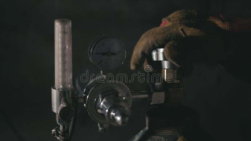 锻造车间 简洁的手工生产 一种带氧焊接的工人开式气瓶容器 黑色电影 库存图片