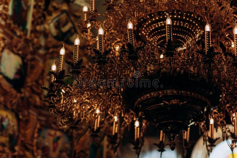镀金的枝形吊灯在老教会里垂悬在象附近 现代灯是象蜡烛 库存图片