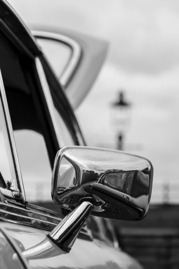 镀铬物被恢复的奥斯汀小游艇船坞的后视镜开放在一次经典汽车集会期间-黑色&白色 图库摄影