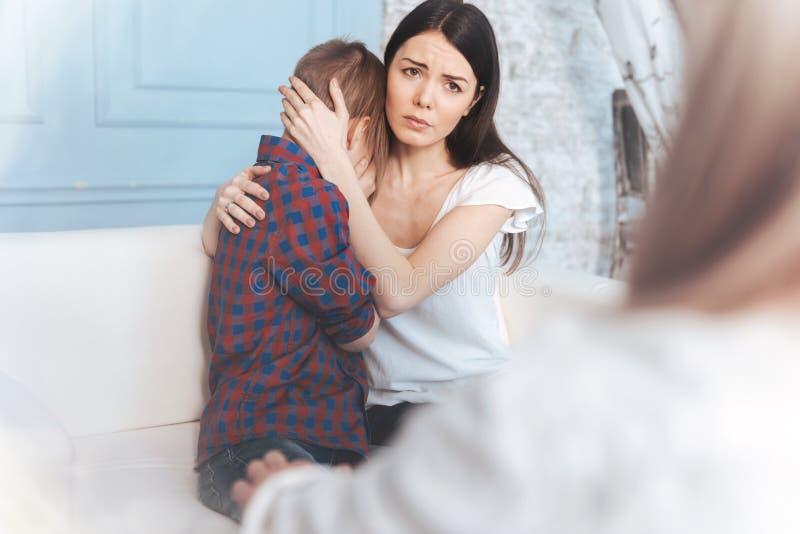 镇定她的儿子的担心的母亲在心理学家办公室 免版税库存图片