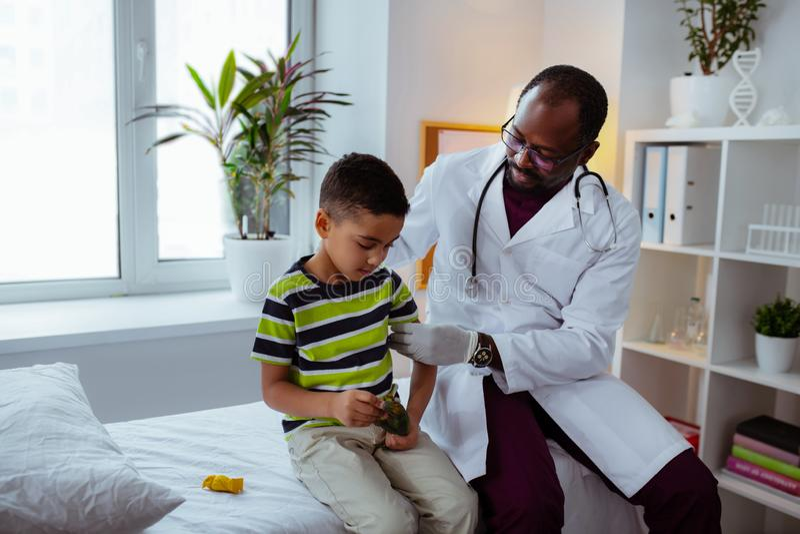 镇定小男孩的深色皮肤的儿科医生在射入前 免版税图库摄影