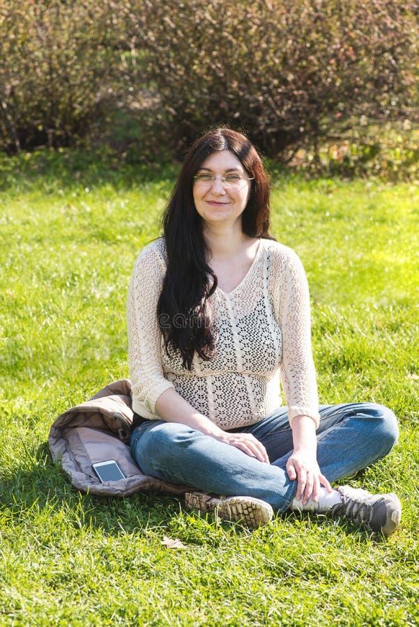 镇定,放松在公园的微笑的孕妇 免版税库存图片