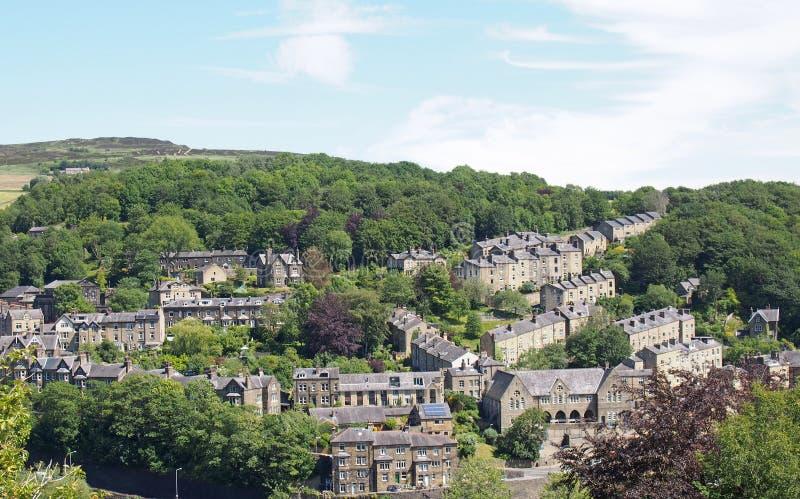 镇的一张风景鸟瞰图在有石房子山坡街道和路的西约克hebden桥梁在树之间 免版税库存图片