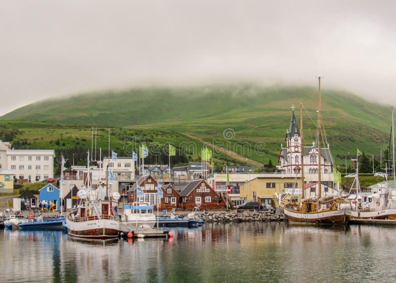 镇胡萨维克美丽如画的全景,五颜六色的房子和教会在海水,冰岛北部反射 免版税库存照片
