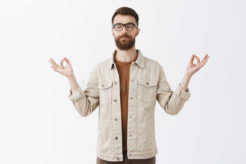 镇静下来与瑜伽 欣慰的平安的悦目都市人画象夹克的有长的病的胡子闭合值的眼睛的 图库摄影