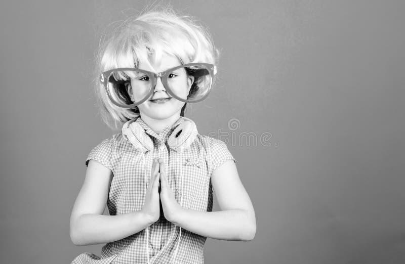 镇静和逗人喜爱 一起扣紧手的逗人喜爱的孩子 戴桃红色假发和花梢眼镜与祈祷的逗人喜爱的女孩 免版税库存照片