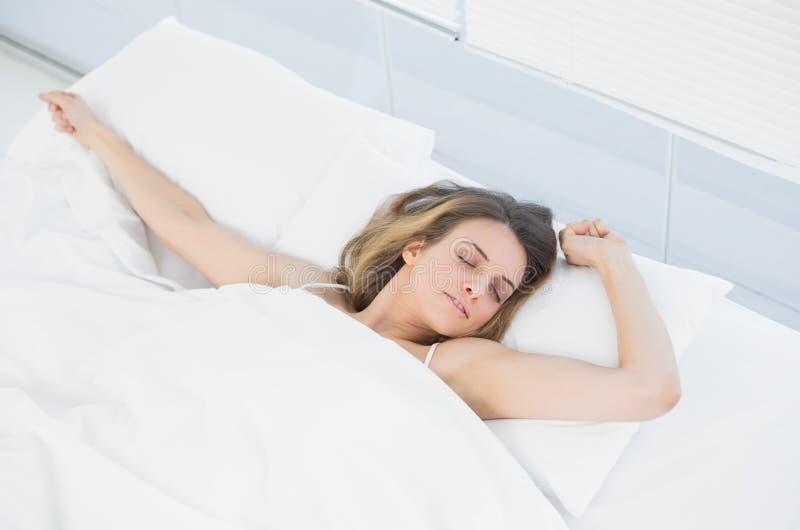镇静妇女小睡的说谎在她的床上的盖子下 免版税库存照片