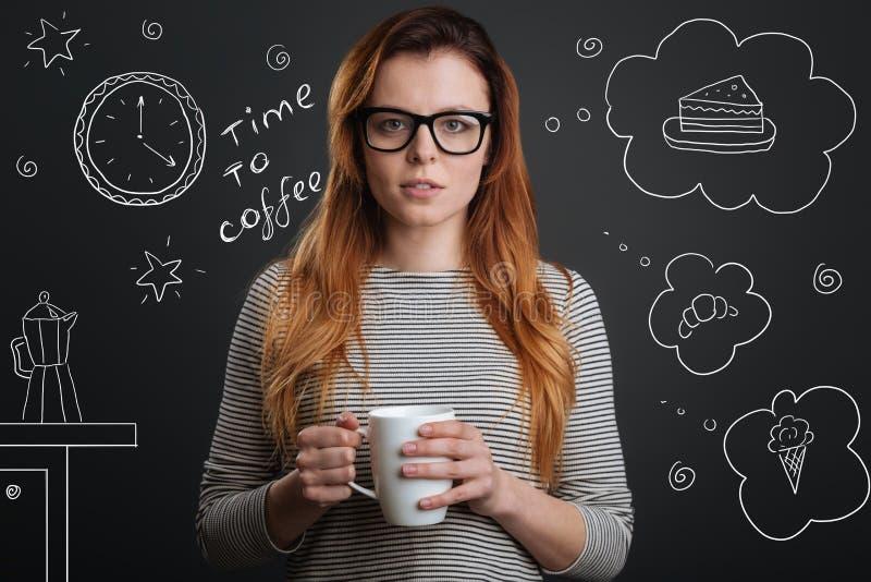 镇静学生饮用的咖啡和选择一个鲜美点心 图库摄影