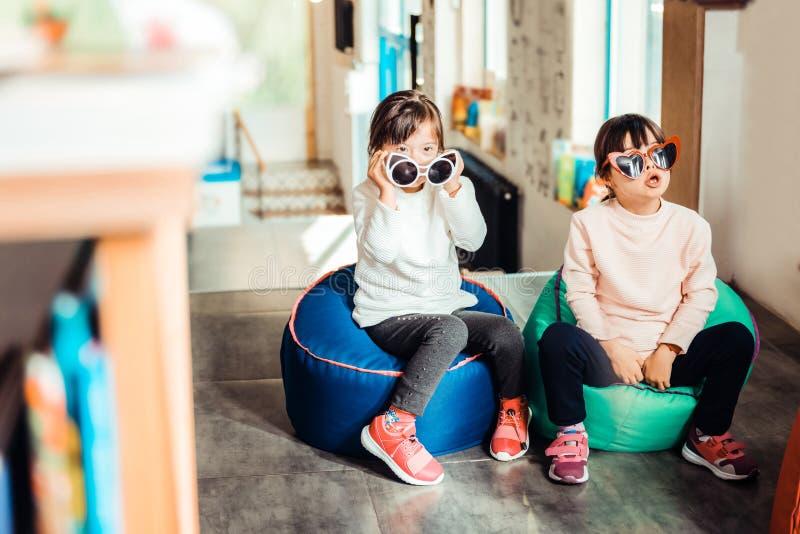 镇静小孩子一起坐扶手椅子 库存图片